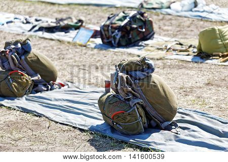 Packed parachutes spread out on the ground