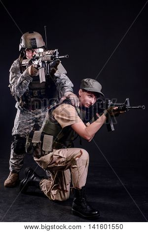 Male and female soldiers in uniform with rifles aim at target on dark background