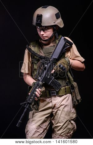 Pretty army girl with riflehelmet and bulletproof vest on black background