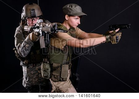 Man in uniform with rifle and woman with gun aims on dark background