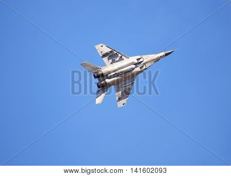 Modern russian fighter flying in a blue sky bottom view