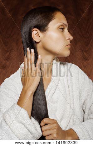 girl in bathrobe petting wet hair her hand