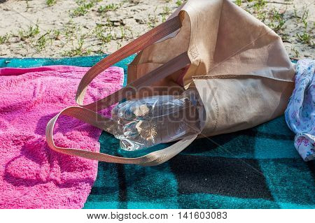 Beach bag and blankets in the sand on the beach.