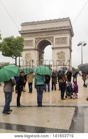PARIS, FRANCE, MAY 20, 2013: people with green umbrellas standing near the Arc de Triomphe, on a rainy day, late afternoon