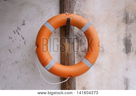 An orange life preserver hanging on a wooden post against a stone wall.