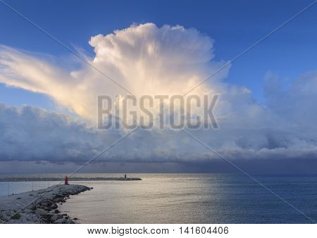 Port of Trani: summer storm at sunset.Apulia,Italy. Breakwater with headlights dominated by stormy cumulus.