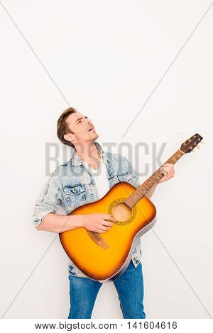 Portrait Of Young Cool Man Plaing On The Guitar And Singing