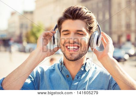 Cheerful Young Man Enjoying  Music With Headphones