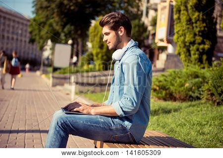 Young Man  Sitting On Bench And Work With Laptop