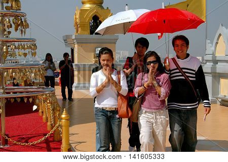 Bangkok Thailand - December 25 2005: Devout Buddhist Thais their hands clasped in prayer circle the upper terrace of the sacred Golden Mount Temple (Phu Khao Thong) shading themselves with umbrellas