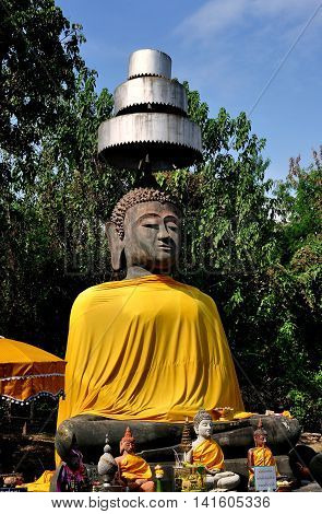 Chiang Mai Thailand - December 30 2012: A large stone Buddha draped in an orange silk robe and covered by a three- tiered metal parasol at Wat That Khao at Wiang Kum Kam Ancient Village