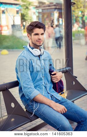 Handsome Young Man Sitting Bus Stop And   Waiting