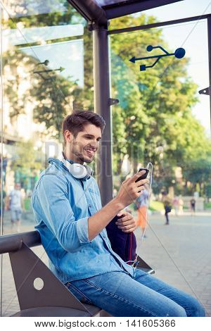 Cheerful Young Man Sitting At Bus Stop And   Waiting