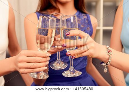 Close up of three women clinking with glasses of shampagne