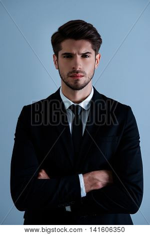 Portrait Of Serious Strict Businessman In Black Suit With Crosed Hands