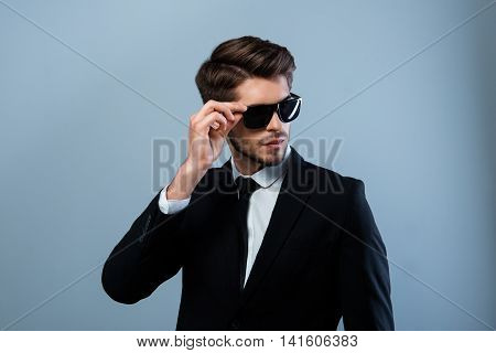Portrait Of Modern Young Businessman In Black Suit And Spectacles