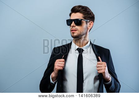 Brutal Hansome Businessman In Glasses Touching His Black Suit