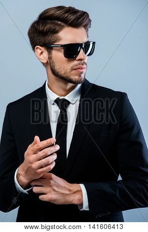 Handsome Businessman In Black Suit And Glasses Fastening Buttons On The Sleeves