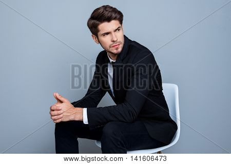 Young Minded Businessman In Black Suit Sitting On Chair