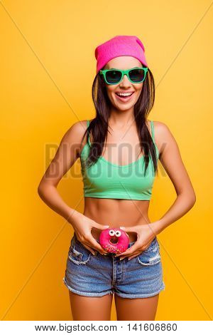 Funny Girl In Pink Hat Holding Pink Donut With Eyes Near Her Waistline