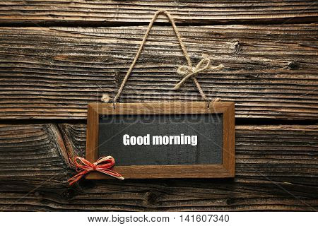 Brown wooden frame on brown wooden background, good morning
