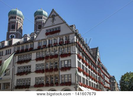 MUNICH, GERMANY - AUGUST 29, 2015: The Hirmer house with its beautiful decoration is the largest men's fashion house in the world in the background are the towers of the Frauenkirche (Cathedral of Our Dear Lady