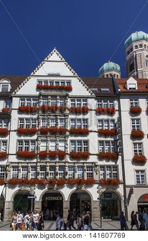 MUNICH, GERMANY - AUGUST 29, 2015: The Hirmer house with its beautiful decoration is the largest men's fashion house in the world in the background are the towers of the Frauenkirche (Cathedral of Our Dear Lady and unidentified people are walking along