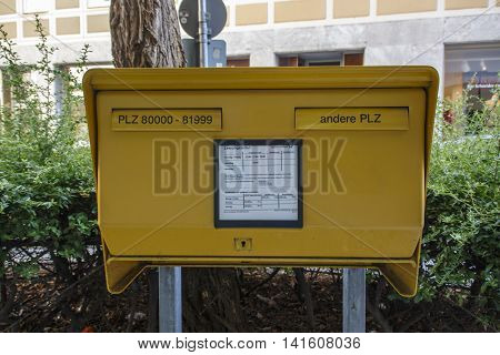 MUNICH, GERMANY - AUGUST 29, 2015: Typical German yellow letterbox in Munich with two slots divided by postal code (for local and for global deliveries)