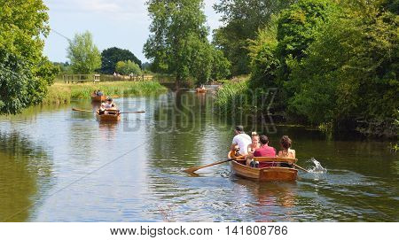 DEDHAM, ESSEX, ENGLAND - AUGUST 06, 2016: People rowing boats on the river Stour on the Essex - Suffolk border enjoying the summer sunshine.