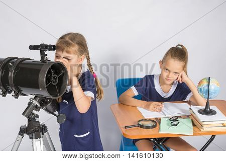 Girl Astronomer Looks At The Sky Through A Telescope, The Other Girl Is Sitting At The Table