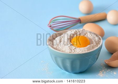 Bowl with flour and yolk domestic eggs egg whisk on blue background