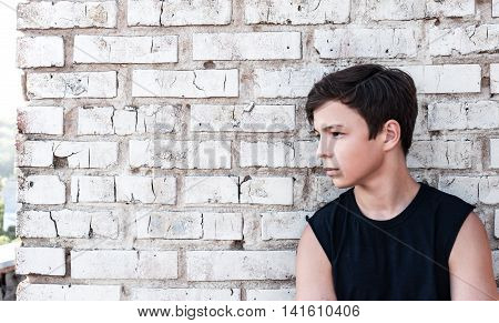 pensive teenager stands near of brick wall