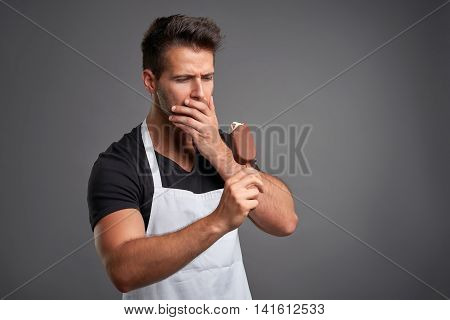 A handsome young barista man having a toothache while eating an ice-cream