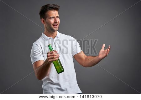 A handsome young man feeling disbelief and looking questioningly while holding a beer