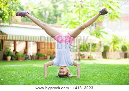 Young girl performing headstand in park on green grass