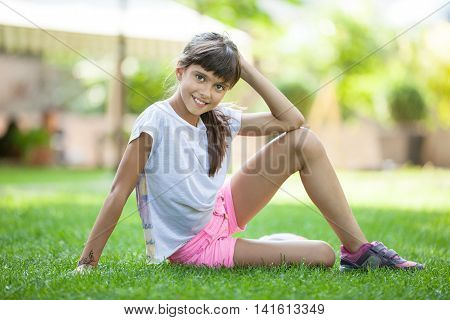 Cheerful cute young girl sitting on the green  grass