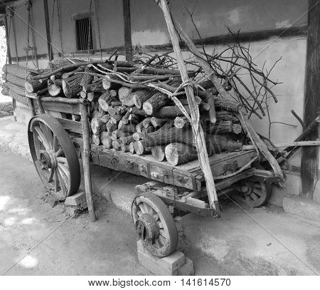 Rustic Wagon Filled with Chopped Wood, next to an Old Wall with Hanging Straw Mats
