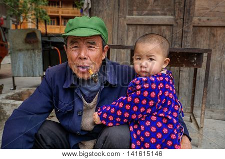 Zhaoxing Dong Village Guizhou Province China - April 9 2010: Three year child hugging an elderly man who holds in his mouth pipe smoking.