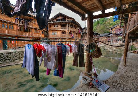 Zhaoxing Dong Village Guizhou Province China - April 9 2010: Erasing underwear dries on under a canopy outdoors hanging on hanger near a rural river and wooden farmhouses local peasants.