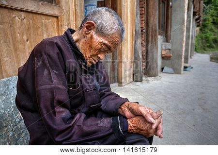 Zhaoxing Dong Village Guizhou Province China - April 9 2010: Aged Chinese man is sleeping while sitting under the open sky on a rural street.