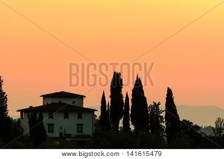 Beautiful Tuscan Casa house perched on a hillside in Tuscany with poplar and olive trees silhouetted against a warm orange sunset sky and the Tuscan Hills in the background