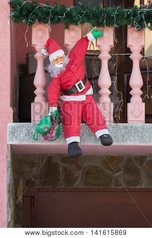 A toy of a Santa Claus climbing on the balcony with a sack of gifts for children