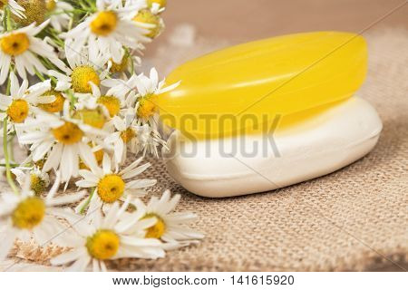 Chamomile handmade soaps on the fabric of jute with chamomile flowers