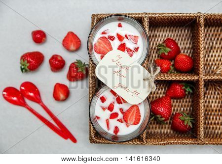 Two Glasses of Yogurt,Red Fresh Strawberries in the Rattan Box with Wish Card,Plastic Spoons on the White Paper.Breakfast Organic Healthy Tasty Food.Cooking Vitamins Ingredients.Summer Fruits.Top View