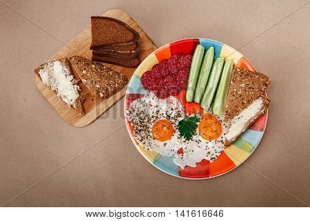Delicious Breakfast from Eggs,Bread with Butter Sausage on the Colorfull Plate.Coffee,Red Juice with White Flowers.Brown Background.Top View