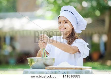 Happy little chef whipping eggs in a bowl outdoors