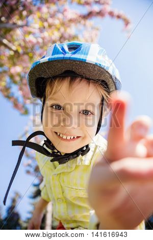 Young boy in helmet looking at camera and going to touch it