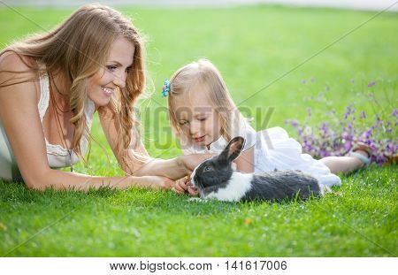 Young woman and her daughter playing with a pet rabbit in a park