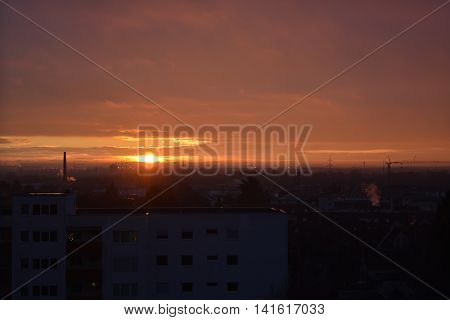 Sunrise in Hattersheim, Hessen, with clouds, a factory chimney and electricity pylons.
