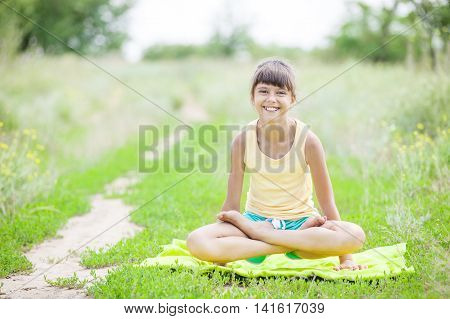 Young girl smiling while sitting in lotus position outdoors